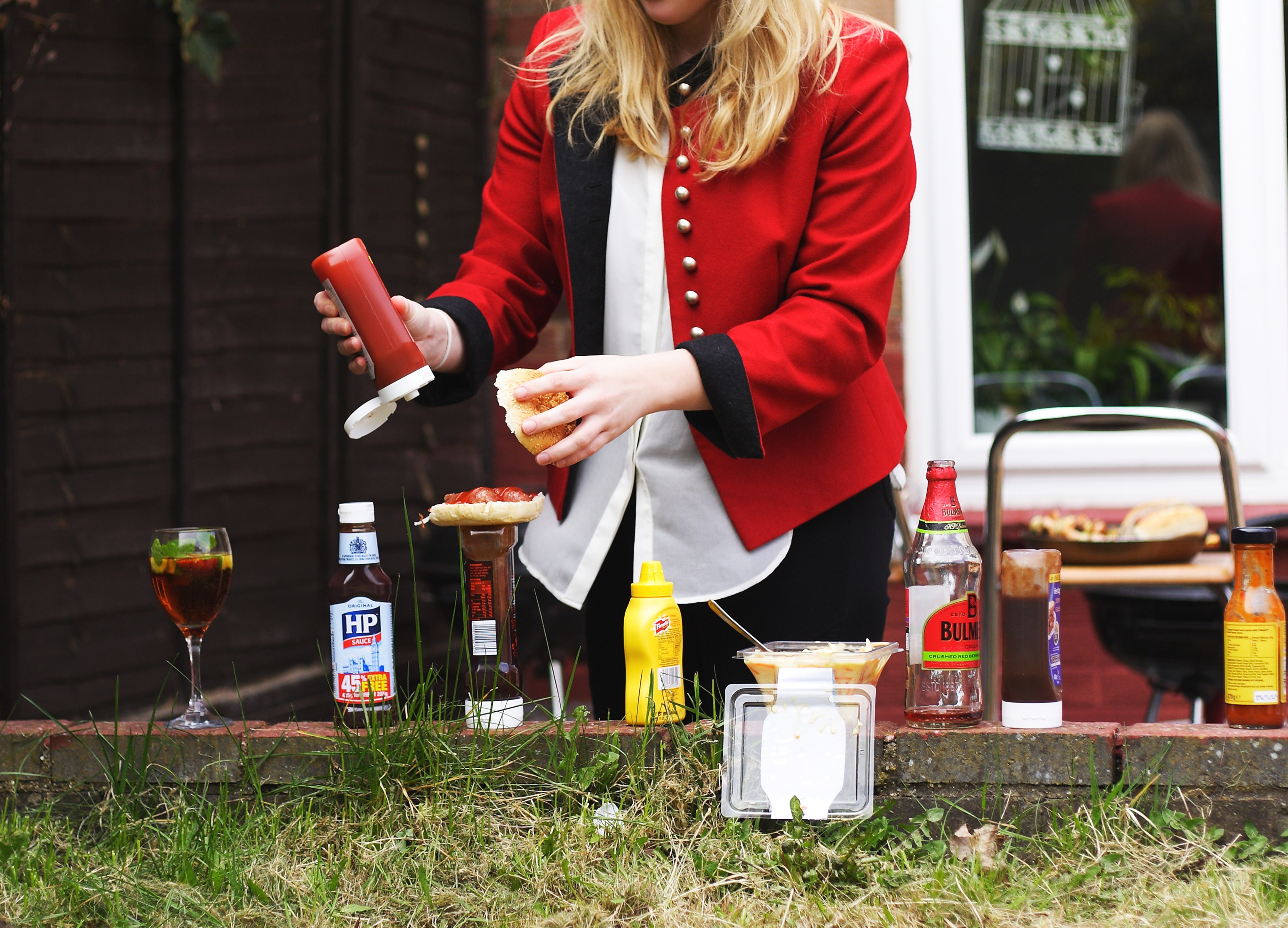 Gesund grillen: Eine Frau gibt Soße auf den Burger
