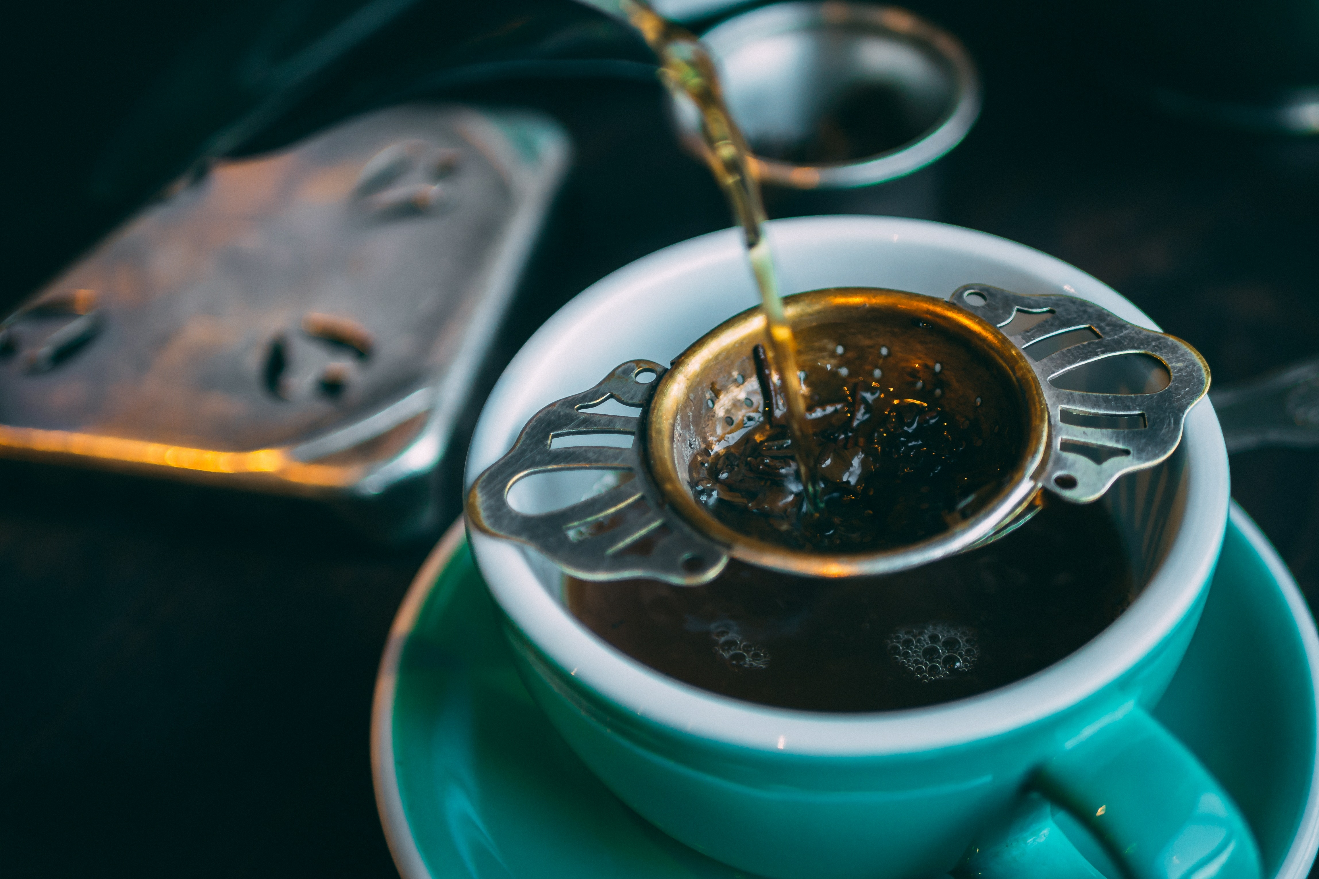 Über ein Sieb wird Tee frisch in der Tasse aufgegossen