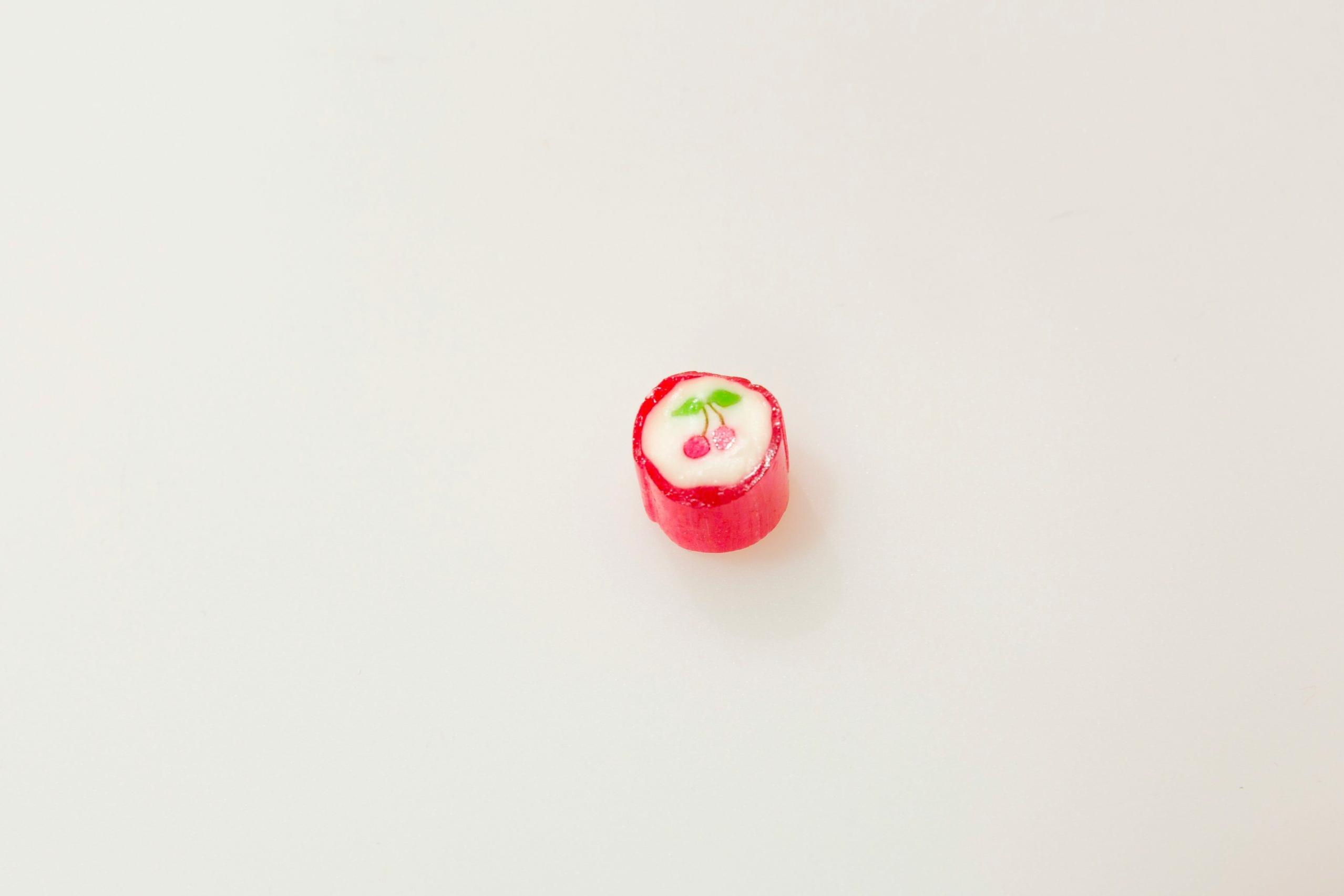 Fasten: Rot-weißes Bonbon mit einer abgebildeten Kirsche auf der Oberseite