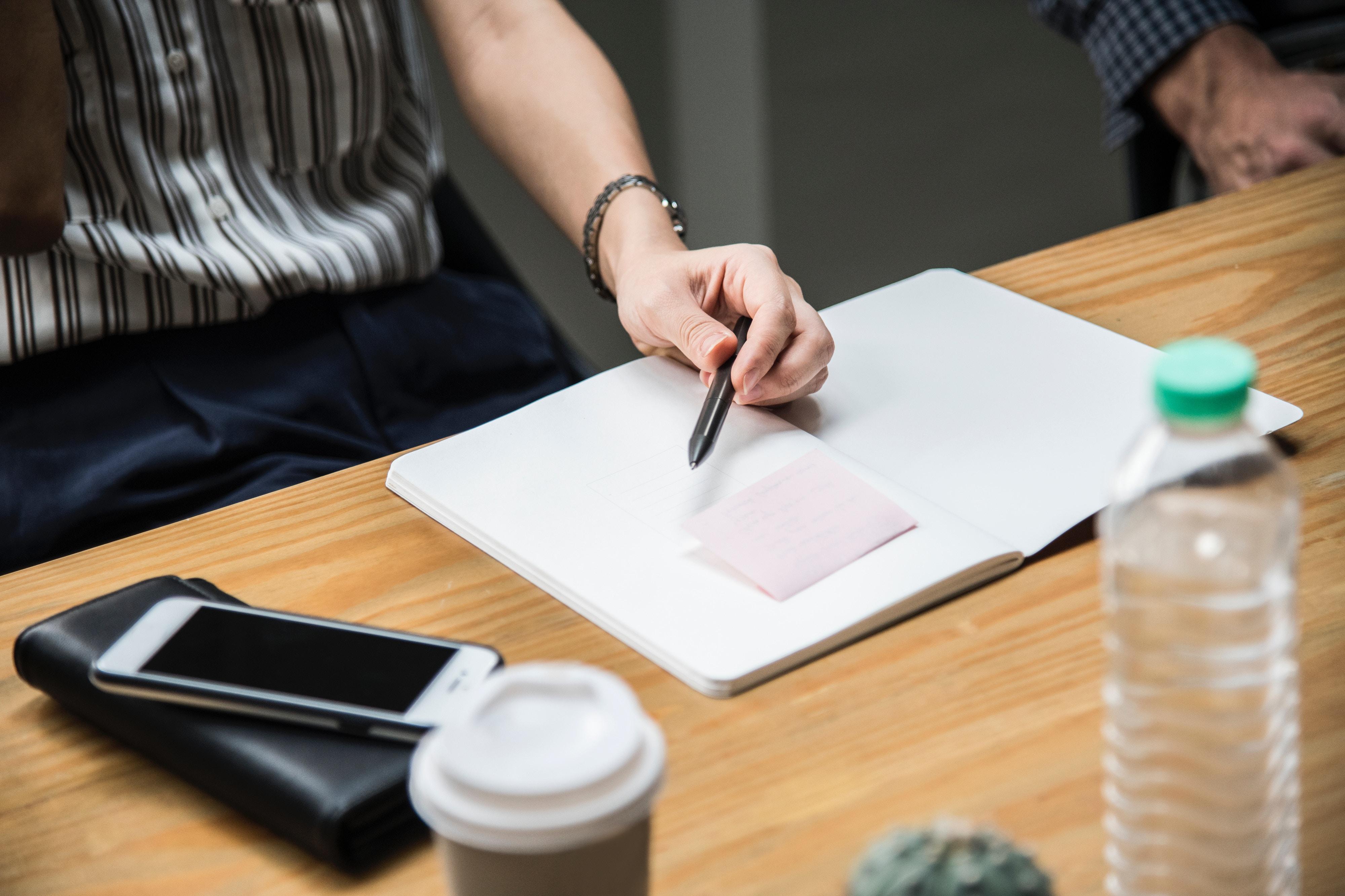 Ernärhung: Frau sitzt am Konferenztisch mit Wasser, Kaffee und Telefon neben sich