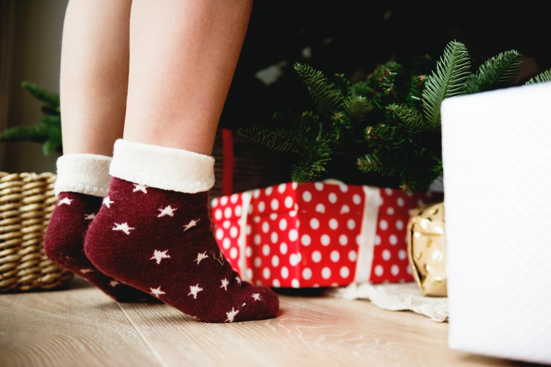 Weihnachtsstress: In Socken vor dem Weihnachtsbaum mit Geschenken darunter