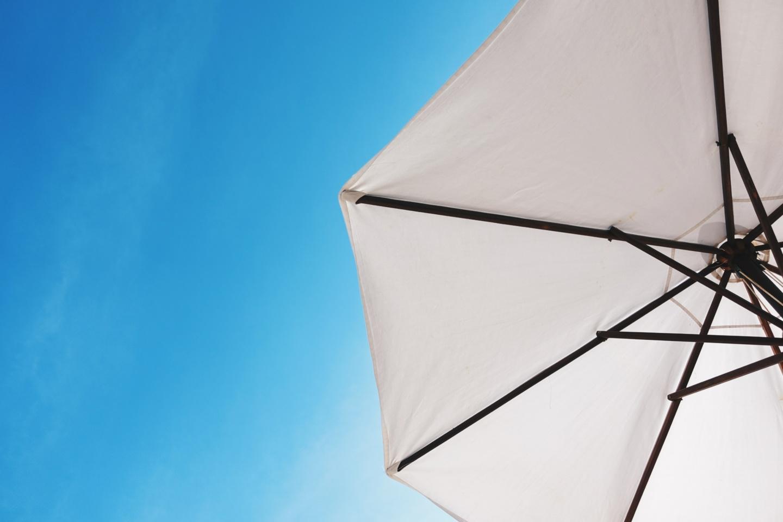 Sonnenschutz: weißer Sonnenschirm vor blauem Himmel