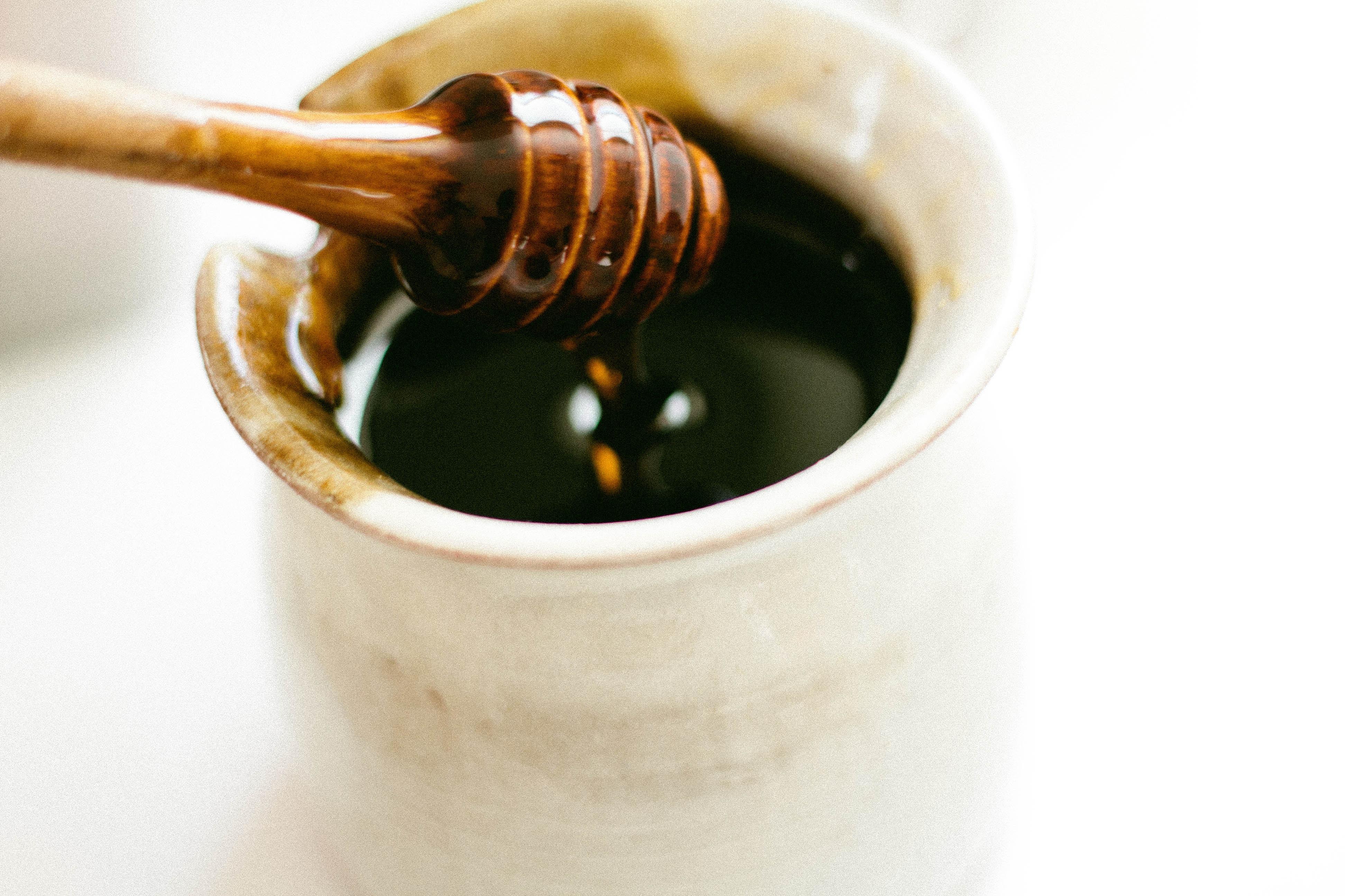 Mit einem Honiglöffel wird Honig in eine Tasse Wasser gerührt