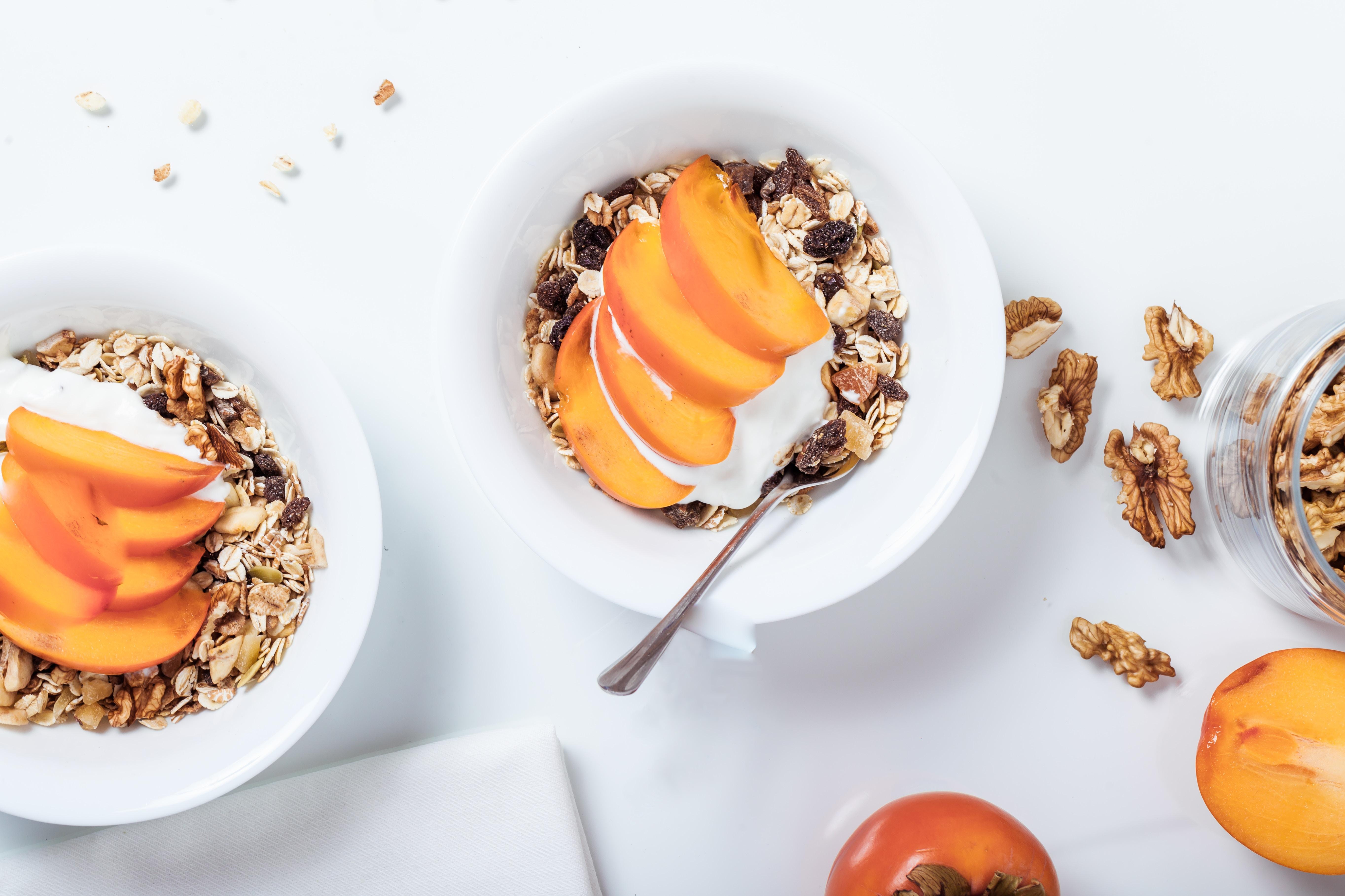 Lunchbox: Schüsseln mit Müsli, Joghurt und aufgeschnittenem Obst auf weißen Untergrund