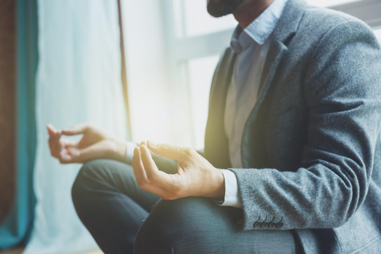 Manager gesund: Mann im Anzug meditiert im Lotussitz