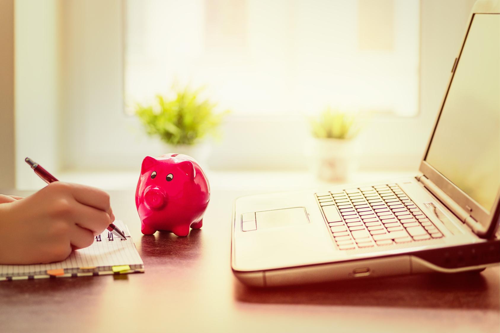 Ein rotes Sparschwein auf einem Schreibtsich zwischen einem aufgeklappten Laptop und einer Hand, die einen Stift hält