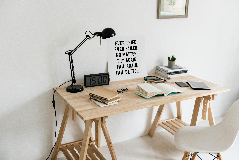Holzschreibtisch vor weißer Wand mit Utensilien und Poster, davor ein weißer Stuhl.