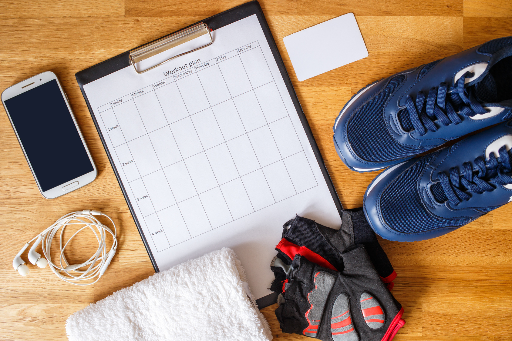 Persönlicher Trainingsplan mit Laufschuhen und Smartphone, daneben andere Fitness-Ausrüstung. Perspektive von oben
