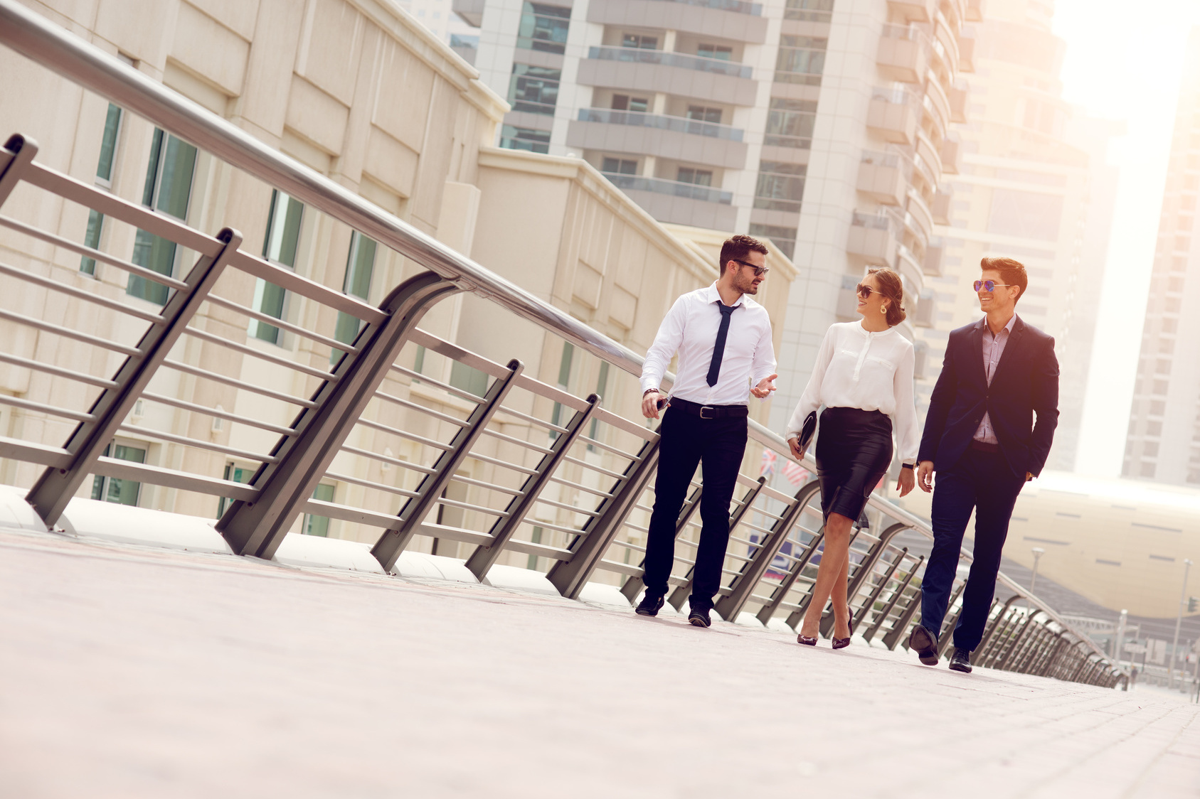 Dresscode: Eine Frau und zwei Männer im Business-Outfit laufen über eine Straße.
