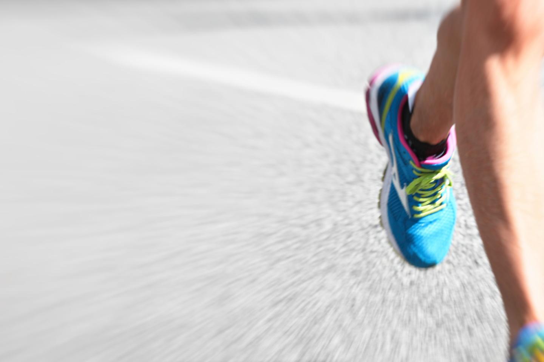 Marathon Planung: Läuferbeine mit bunten Turmschuhen auf Asphaltstraße