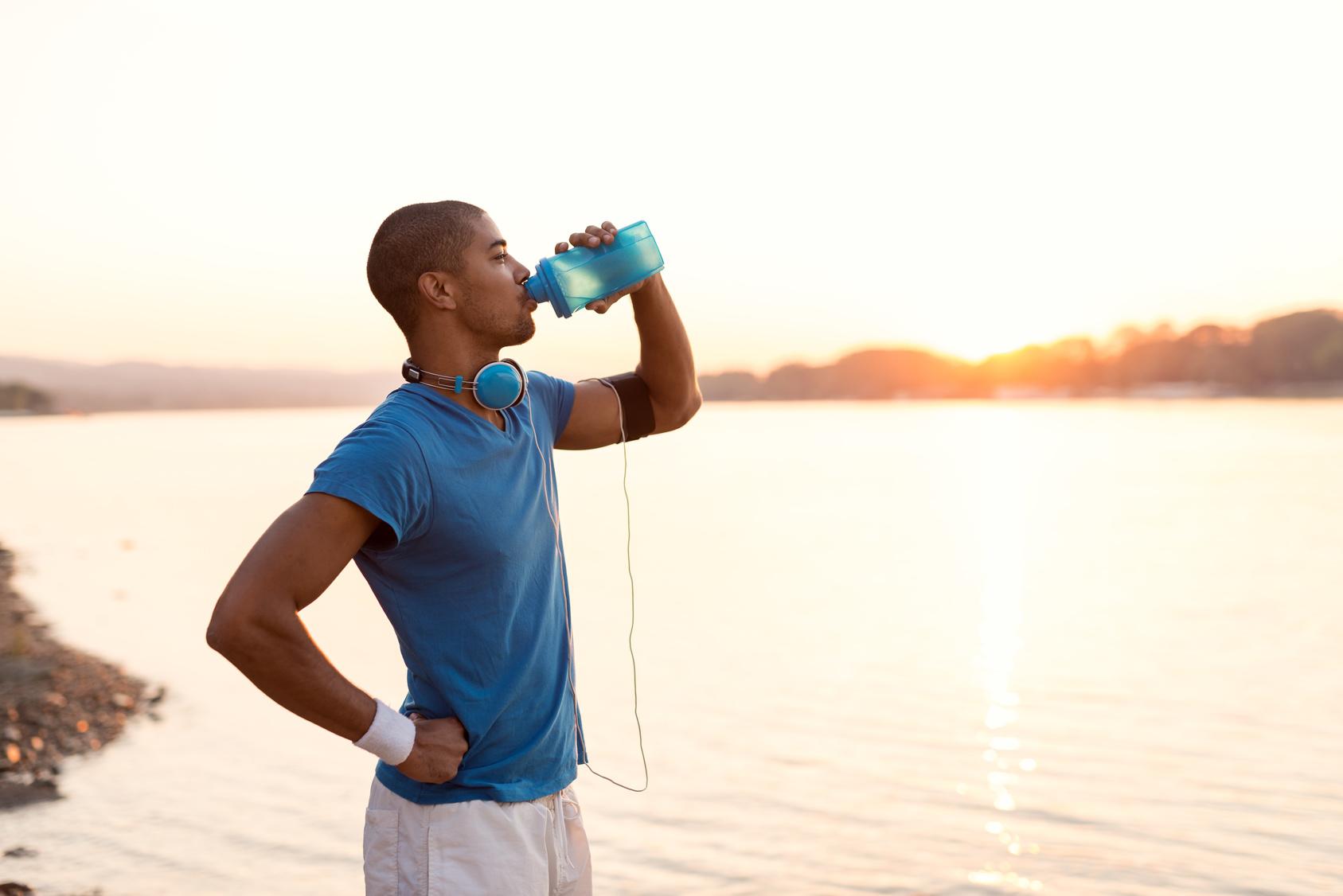 Laufplanung: Ein junger Mann stoppt am See seinen Lauf um Wasser zu trinken