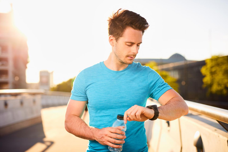 Junger männlicher Läufer checkt seinen Fitness-Tracker während seiner Laufrunde
