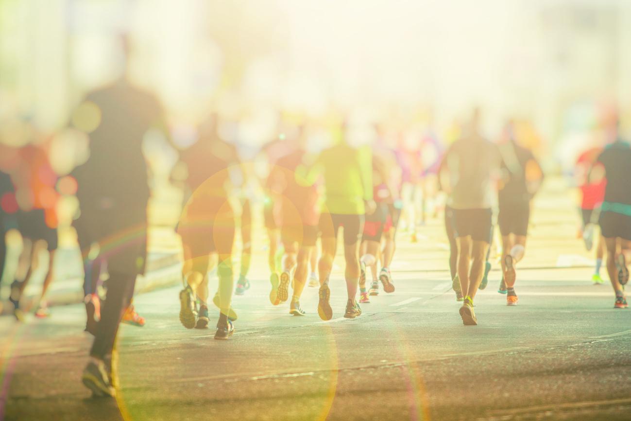 Marathon laufen - Läufer von hinten im Gegenlicht