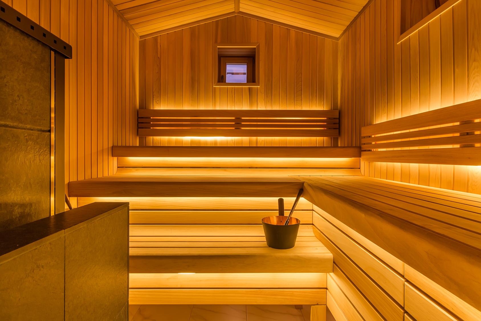 Holzsauna mit drei Sitzebenen, indirekter Beleuchtung und einem Holzgefäß für einen Aufguss.