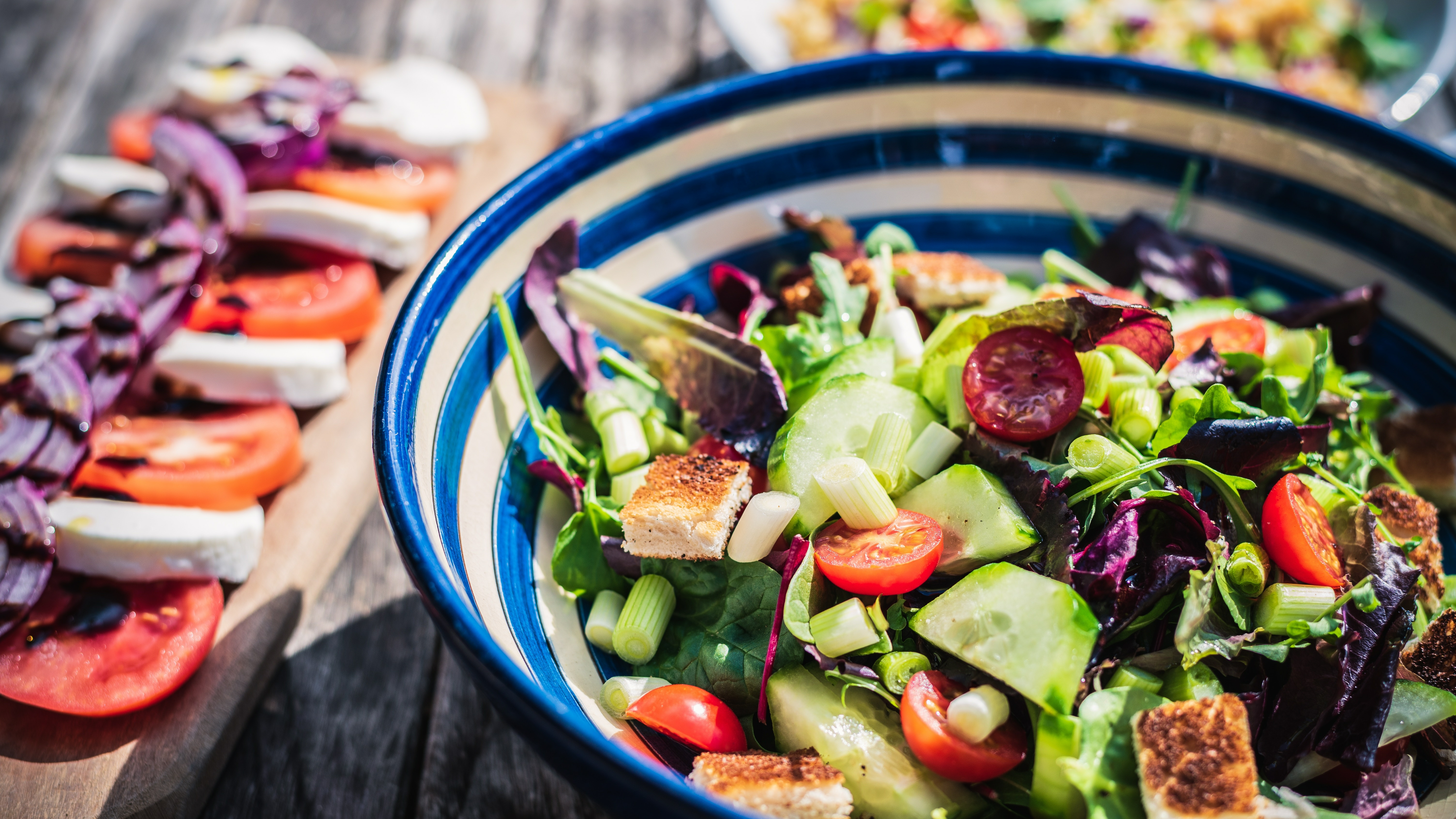 Gesunde Ernährung: Eine blau weiß gestreifte Schüssel mit Salat, daneben ein Brettchen mit Tomate und Mozzarella-Scheiben