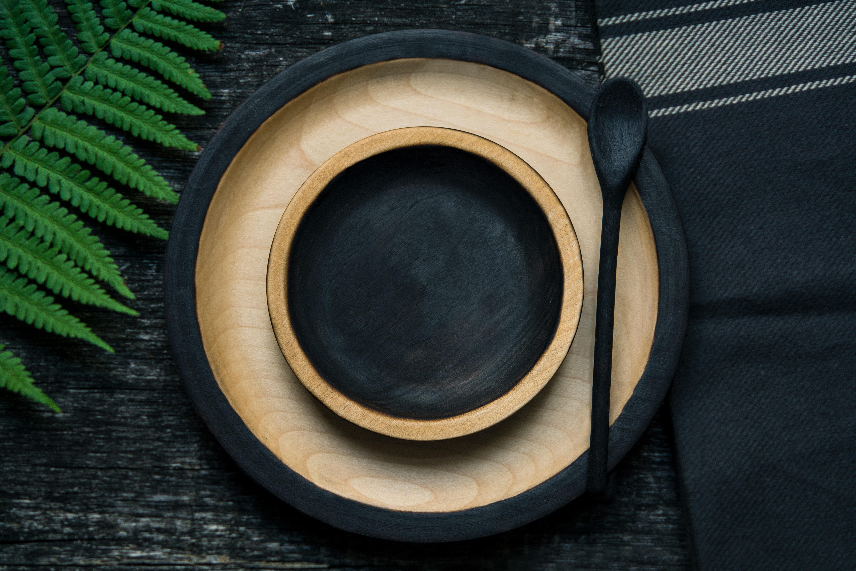Holzschüssel, innen schwarz, auf Holzteller, daneben liegt ein schwarzer Holzlöffel
