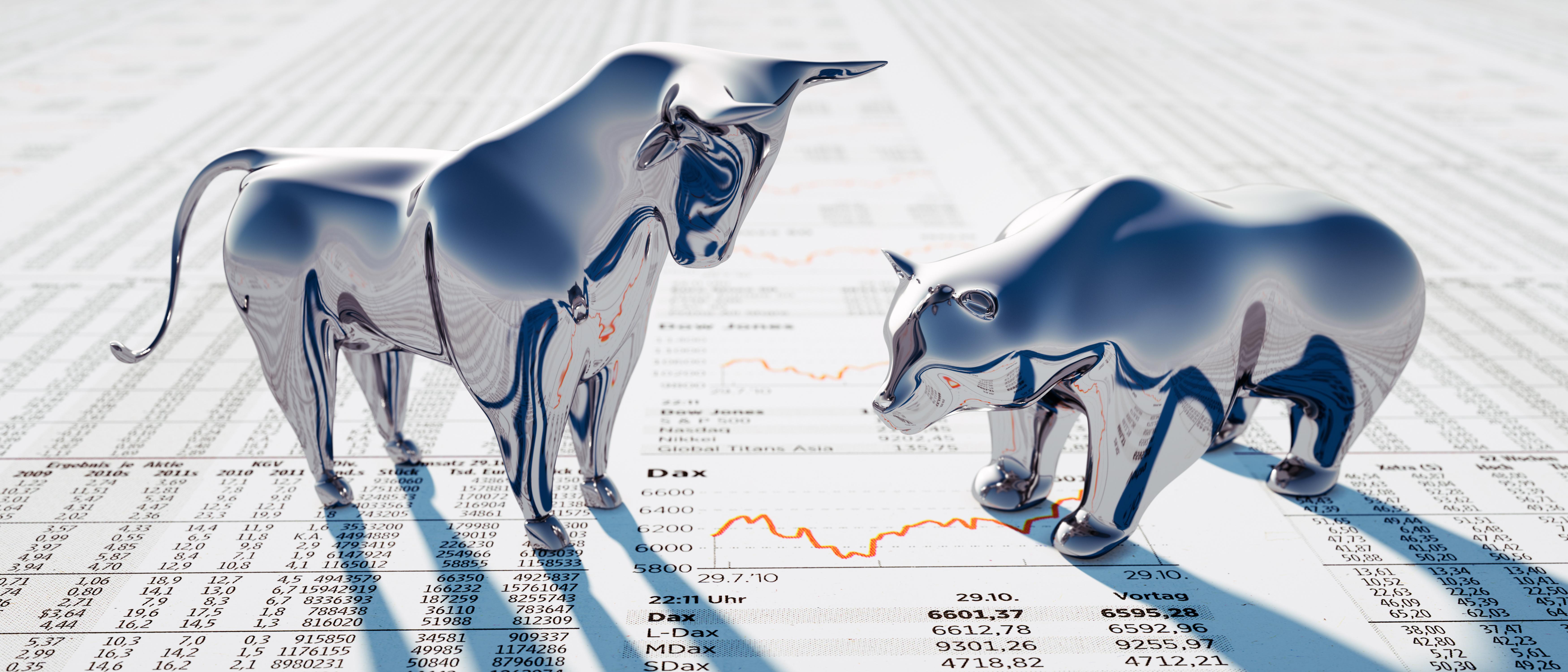 Aktien: Bulle und Bär stehen auf Zeitungsseite mit Aktienkursen