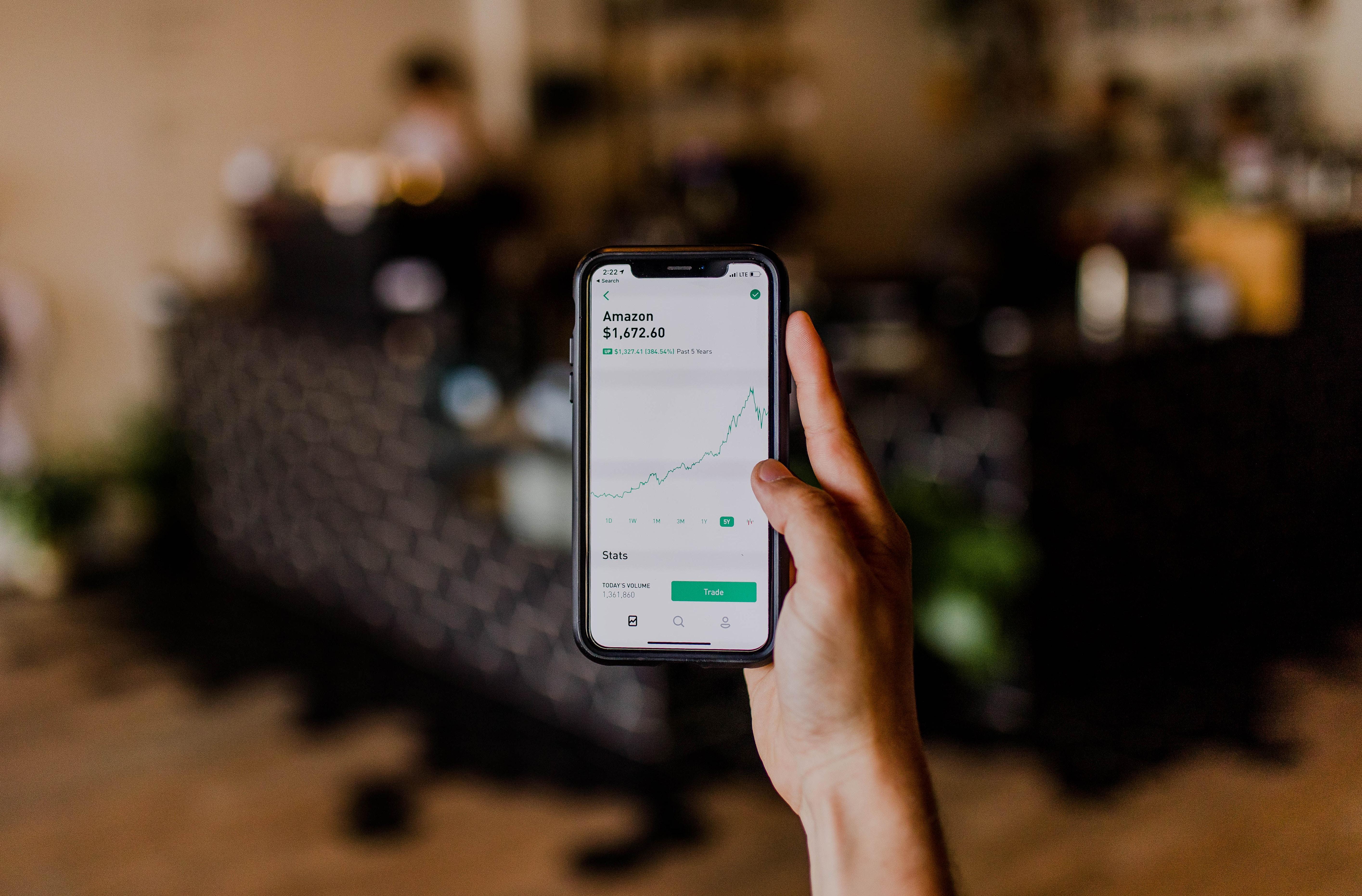 Aktien: Hand hält Smartphone mit Aktienkurs auf dem Display