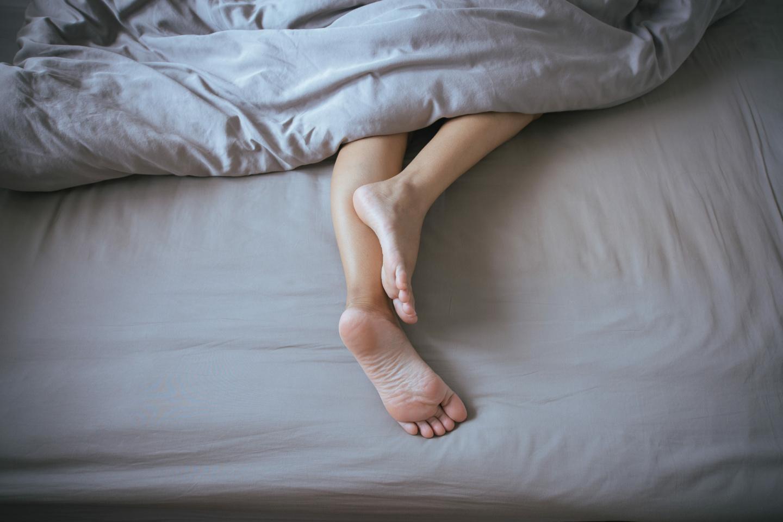Schlafen: Füße und Beine unter der Bettdecke auf dem Bett