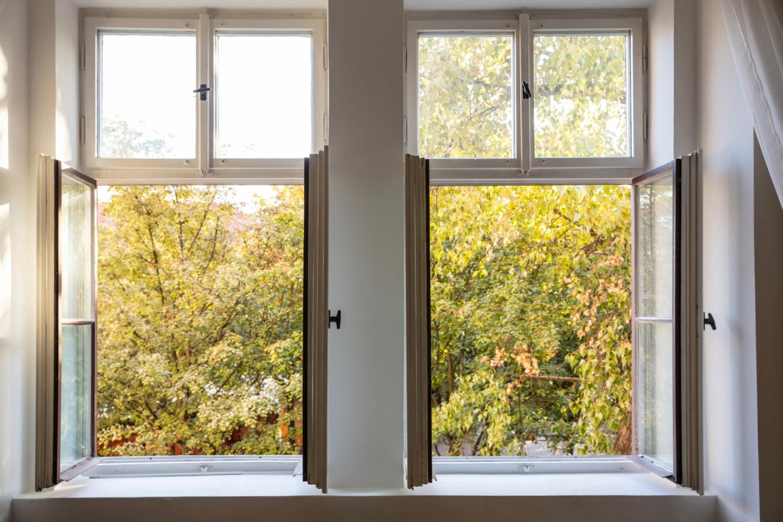 Lüften - Blick durch zwei offen Fenster auf Bäume mit gelbem Herbstlaub