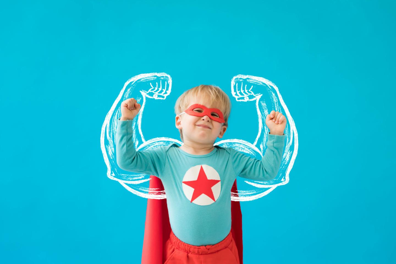 Superfoods: kleiner Junge, als Superheld verkleidet, mit geuzeichneten Armen und Muskeln eines Erwachsenen