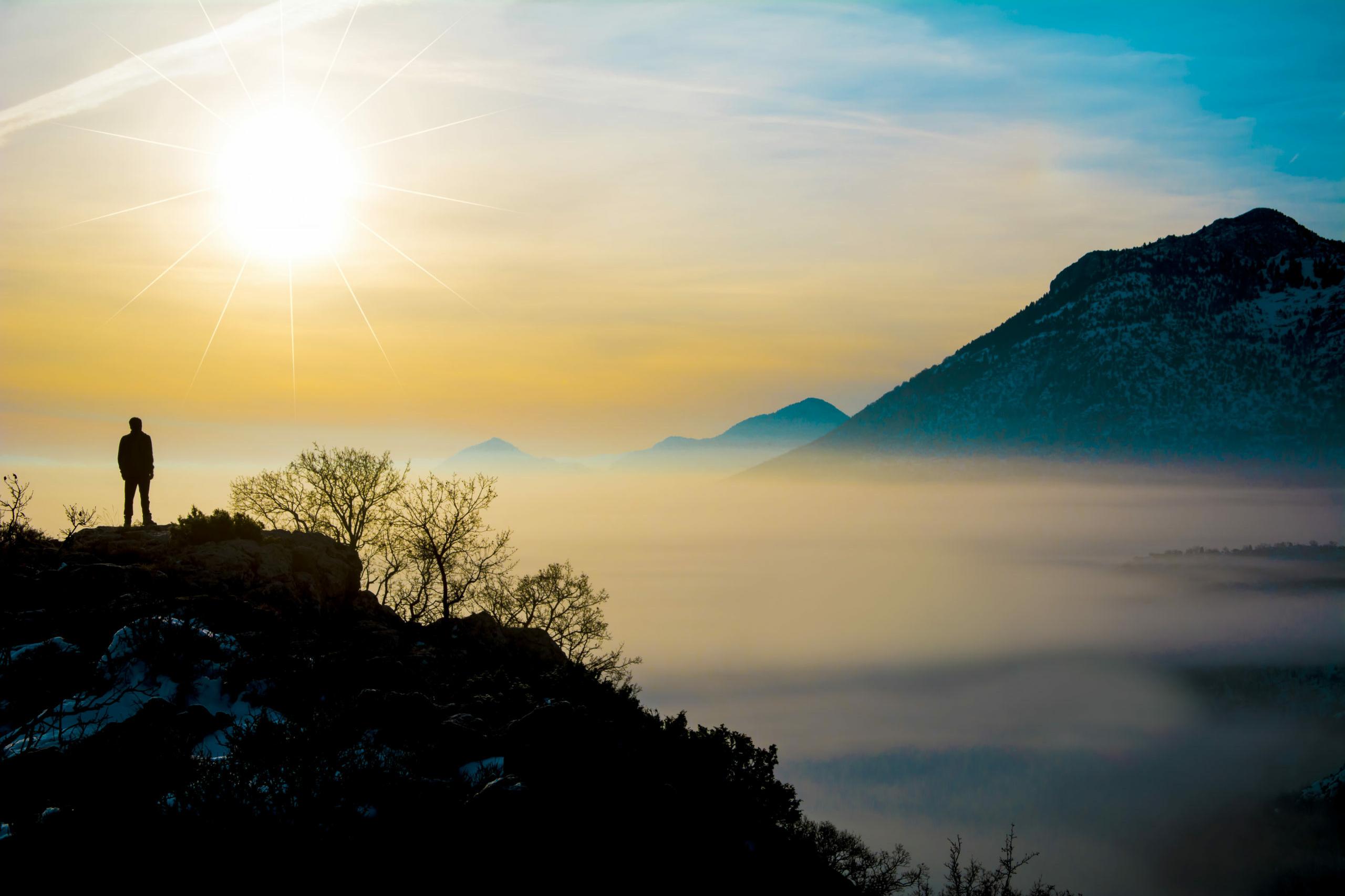 Mann betrachtet einen Sonnenuntergang in den Bergen