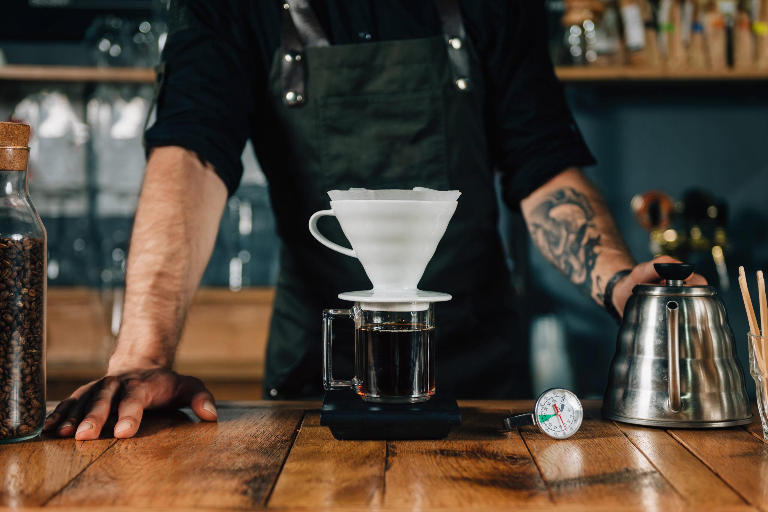 Filterkaffee: Ein Mann brüht Kaffee mit einem Filter auf, Daneben steht eine Kanne und liegt ein Thermometer.