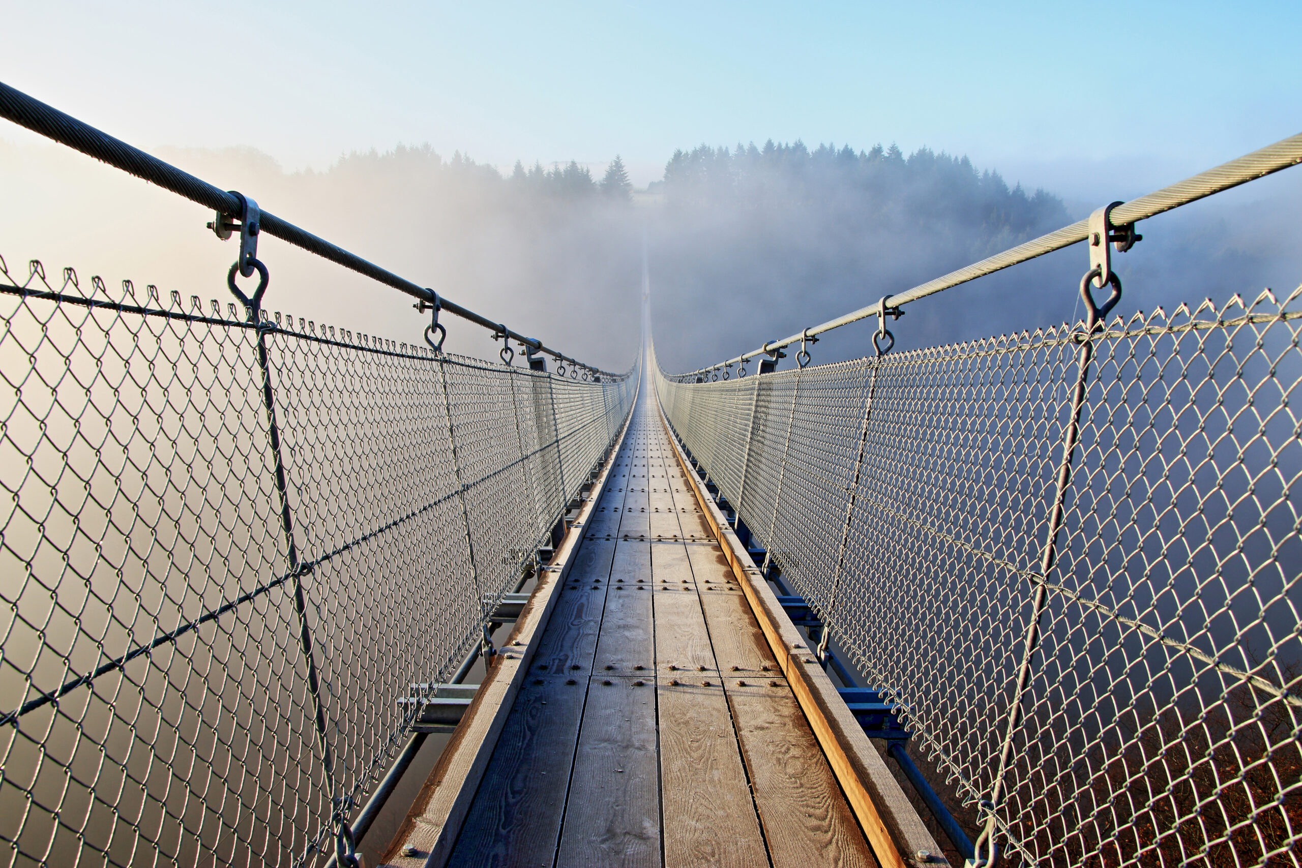 Ziel: Eine Hängebrücke führt auf einen gegenüberliegenden Berg, der im Morgendunst zu sehen ist.