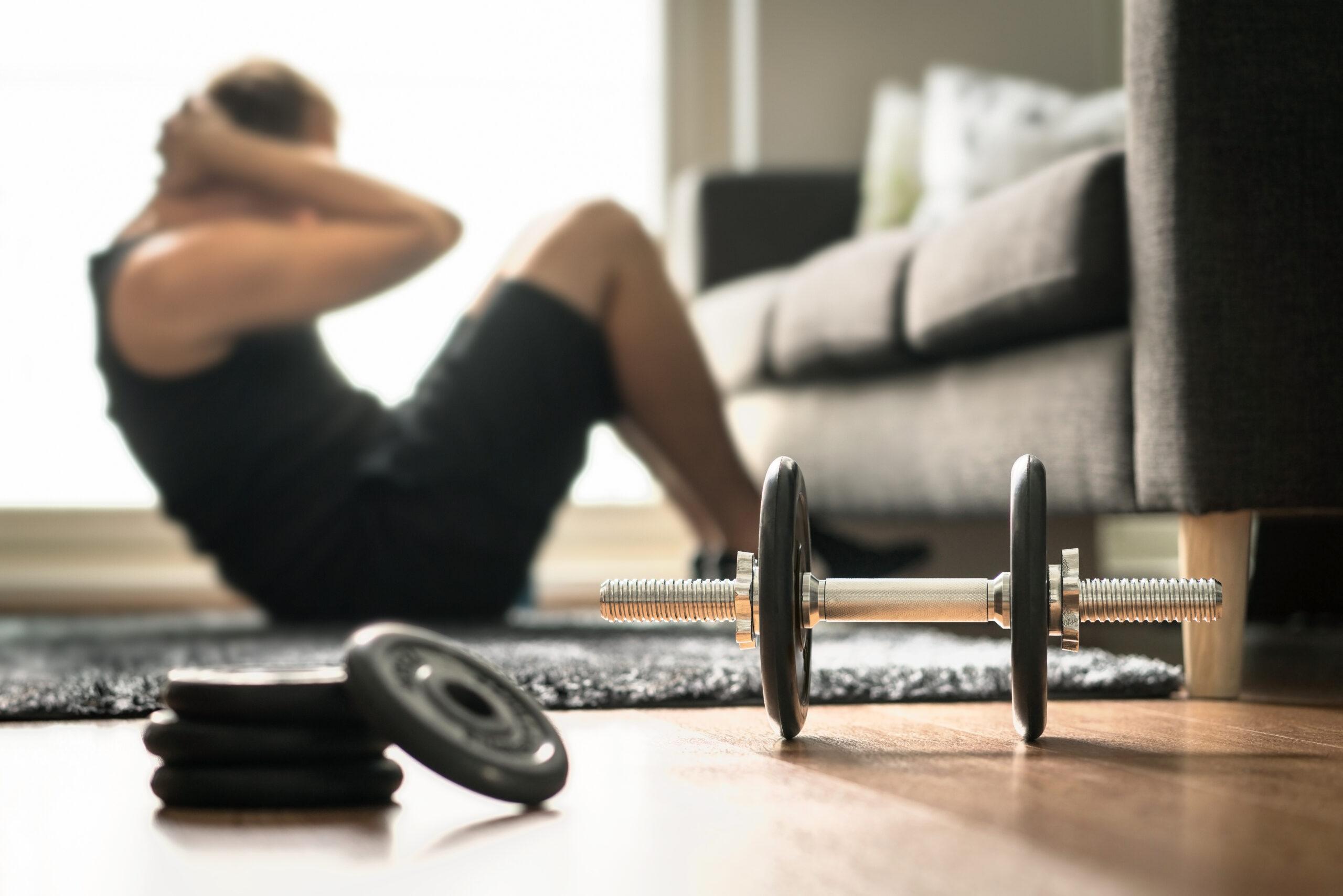 Krafttraining: Ein Mann trainiert Crunches im Wohnzimmer. Neben ihm liegt eine Hantel mit Gewichten zum Workout.