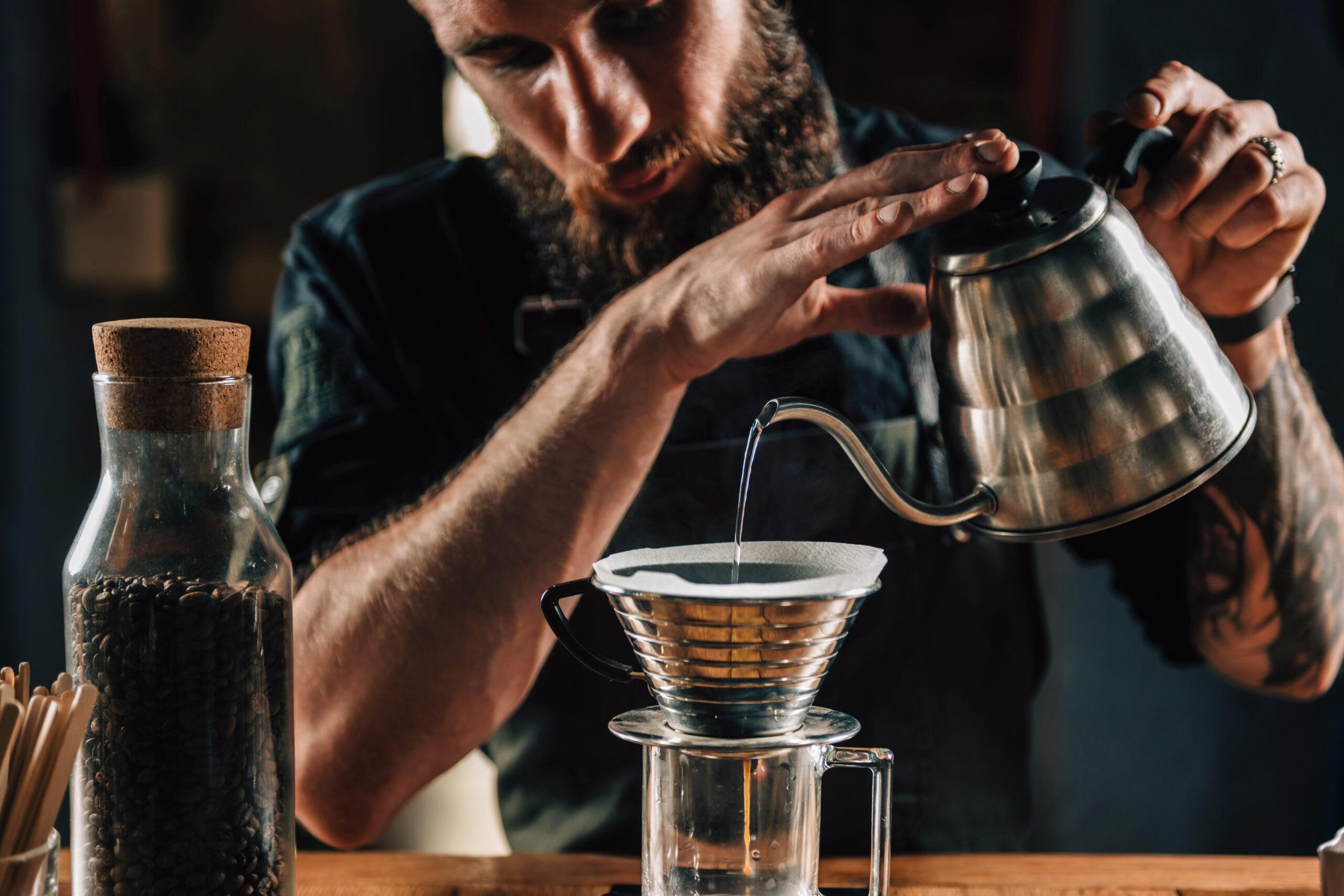 Filterkafffee: Ein Mann gießt Wasser aus einer Edelstahlkanne in ein Glas mit Filteraufsatz. Der Kaffee läuft durch.
