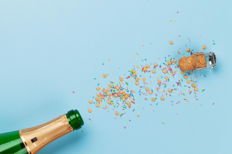 Alkohol: Sektflasche vor blauem Hintergrund. Korken und Konfetti fliegen aus der Flasche