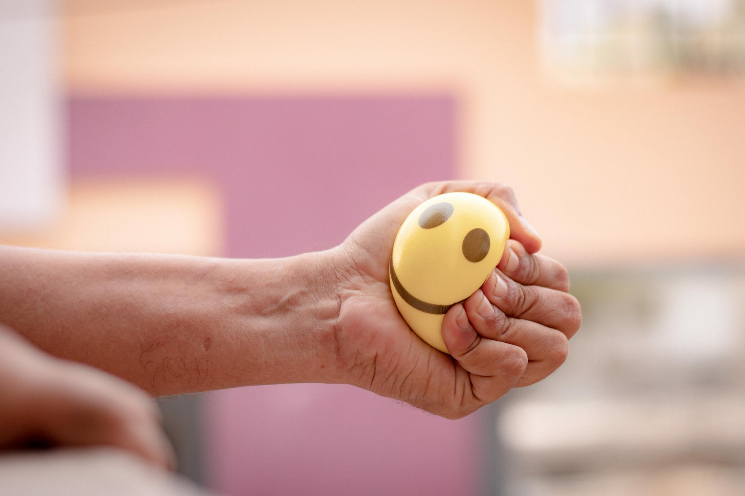 Stress: Eine Hand drückt einen weichen Ball zusammen, um Stress abzulassen.