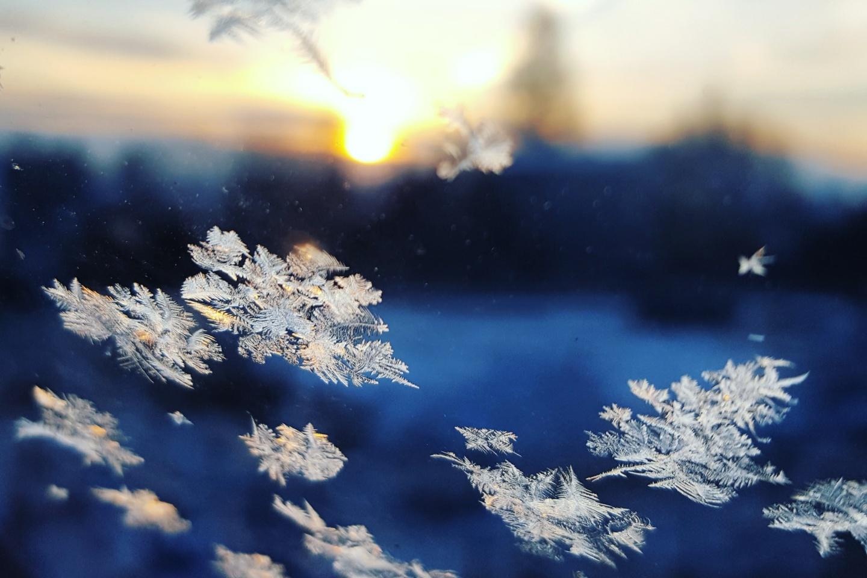 Winterblues: Fenster mit Eiskristallen vor eine verschwommenen Winterlandschaft