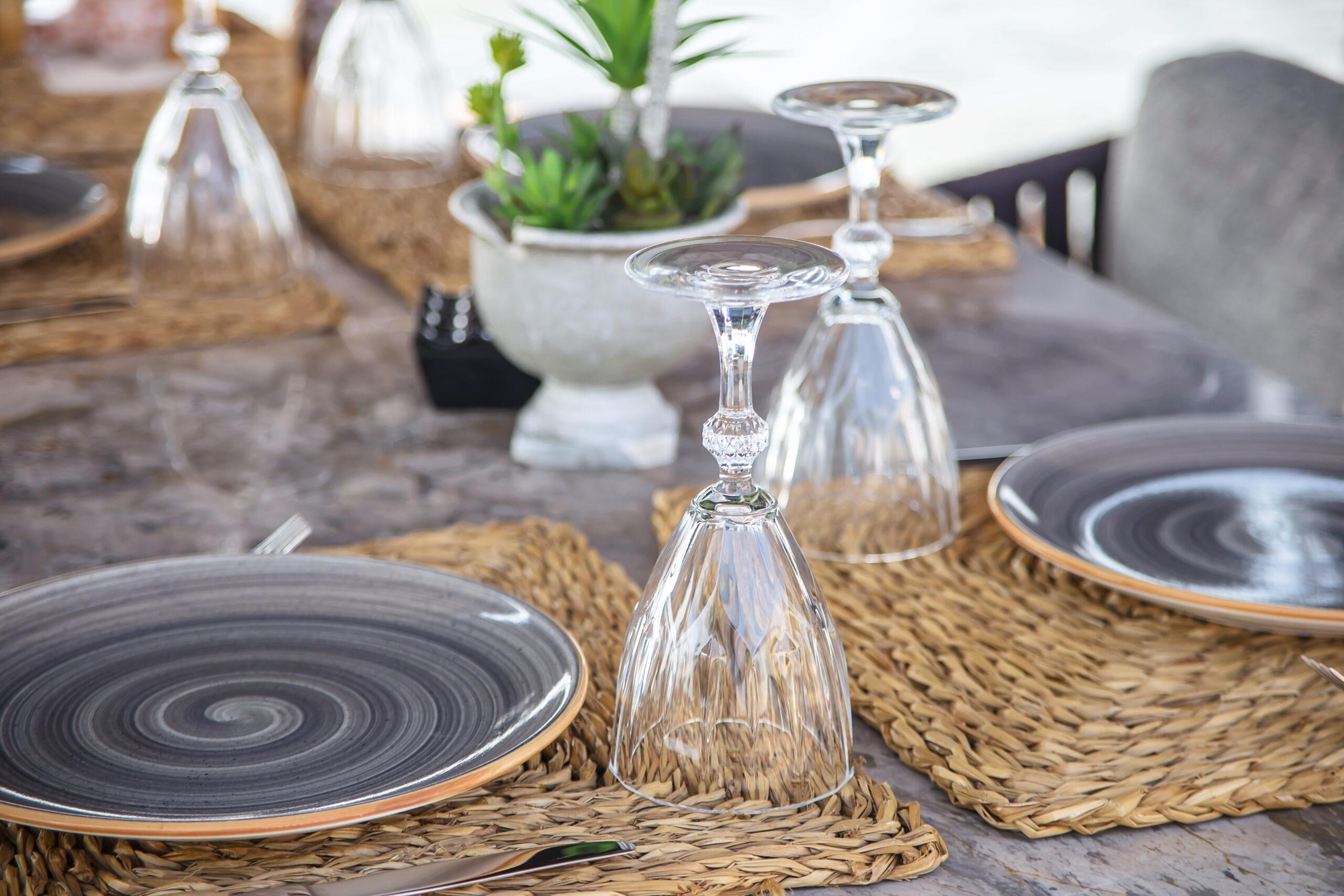 Bedürfnis: Auf einem grauen Holztisch liegen Platzsetz aus Bast. Darauf stehen graue Teller mit Besteck und Gläsern