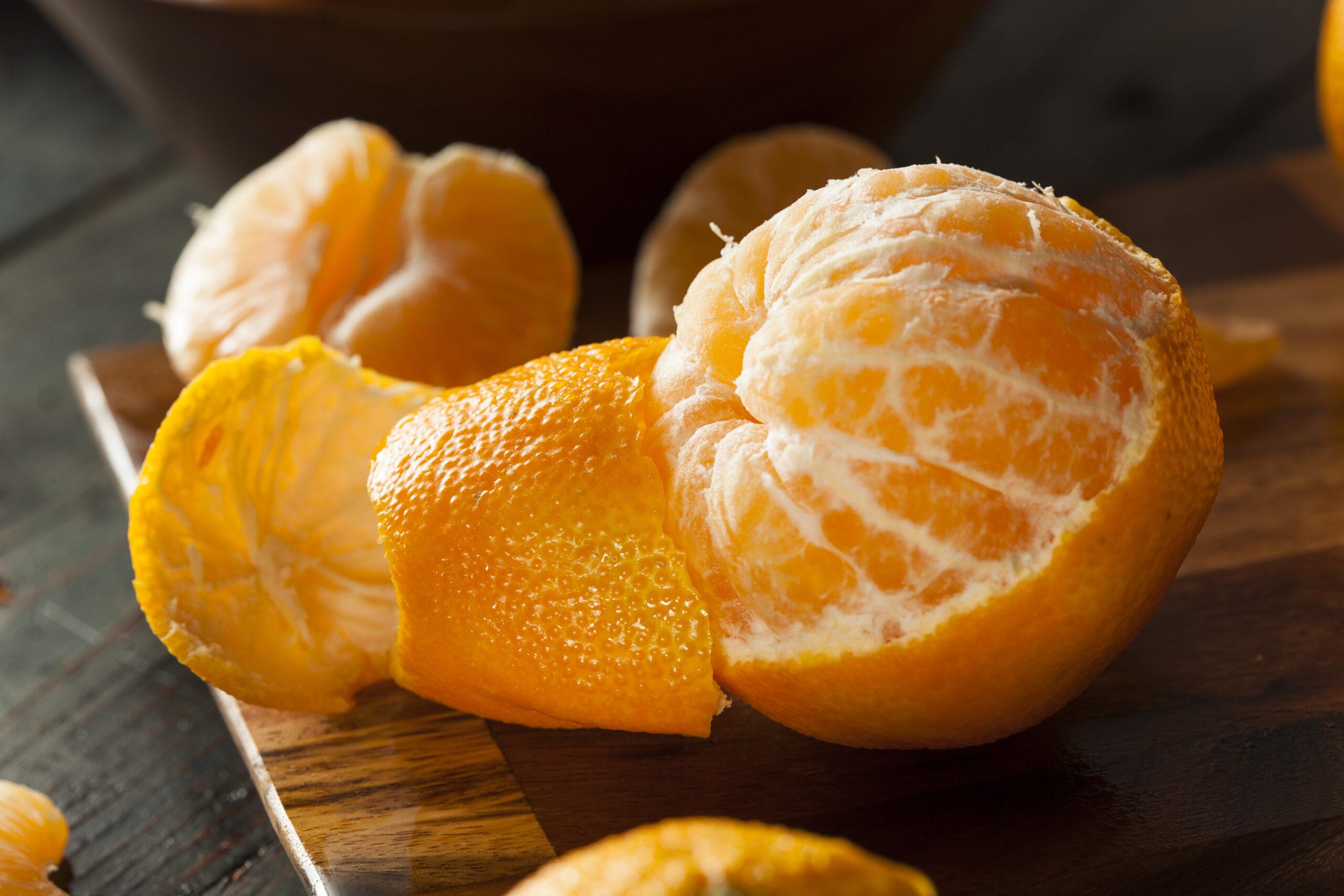Zero-Waste: Mandarine auf einem Holzbrett, die zur Hälfte geschält ist