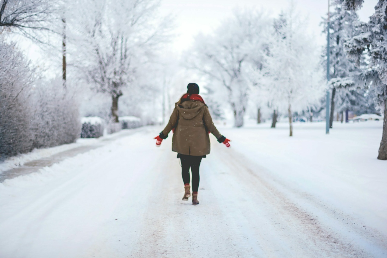 Haut: Eine Frau spaziert über eine verschneite Straße in einem Wohngebiet