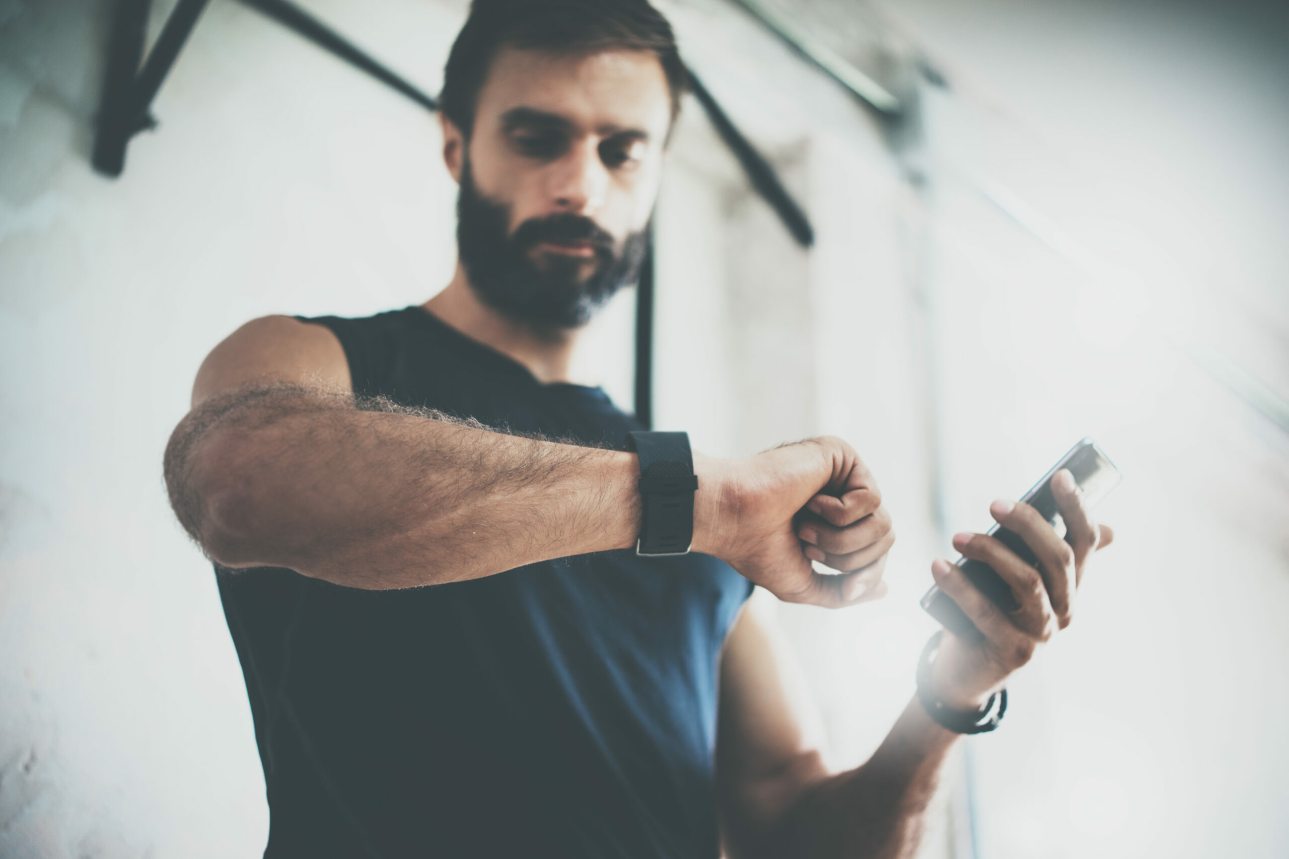 Mann mit Bart checkt Smart-Watch nach Workout