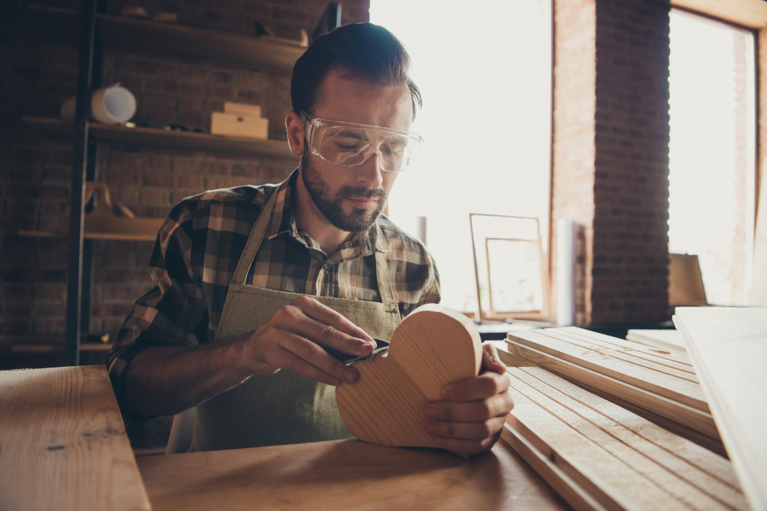 Herz in Form: Mann mit Bart arbeitet konzentriert an einem Holzherz