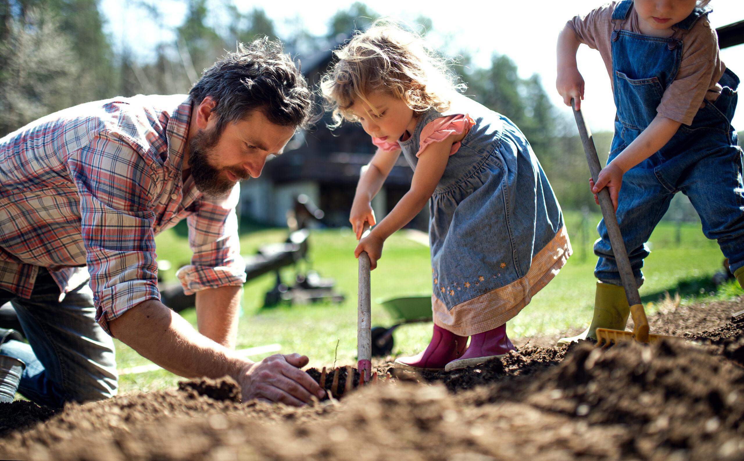 Herz in Form: Vater und Kleinkinder bei der Gartenarbeit