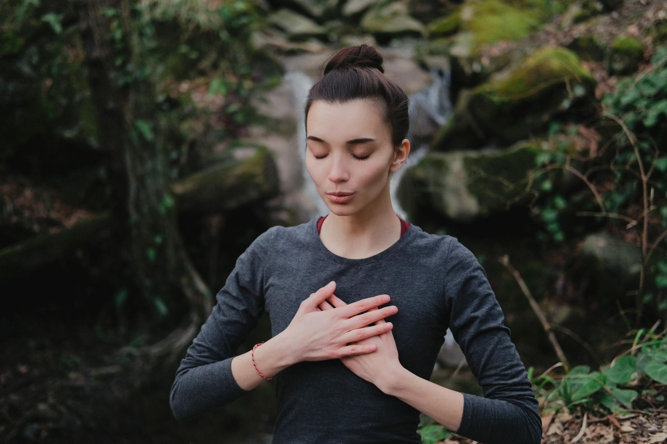 Richtig atmen: Junge Frau bei einer Atemübung vor einem Wasserfall im Wald