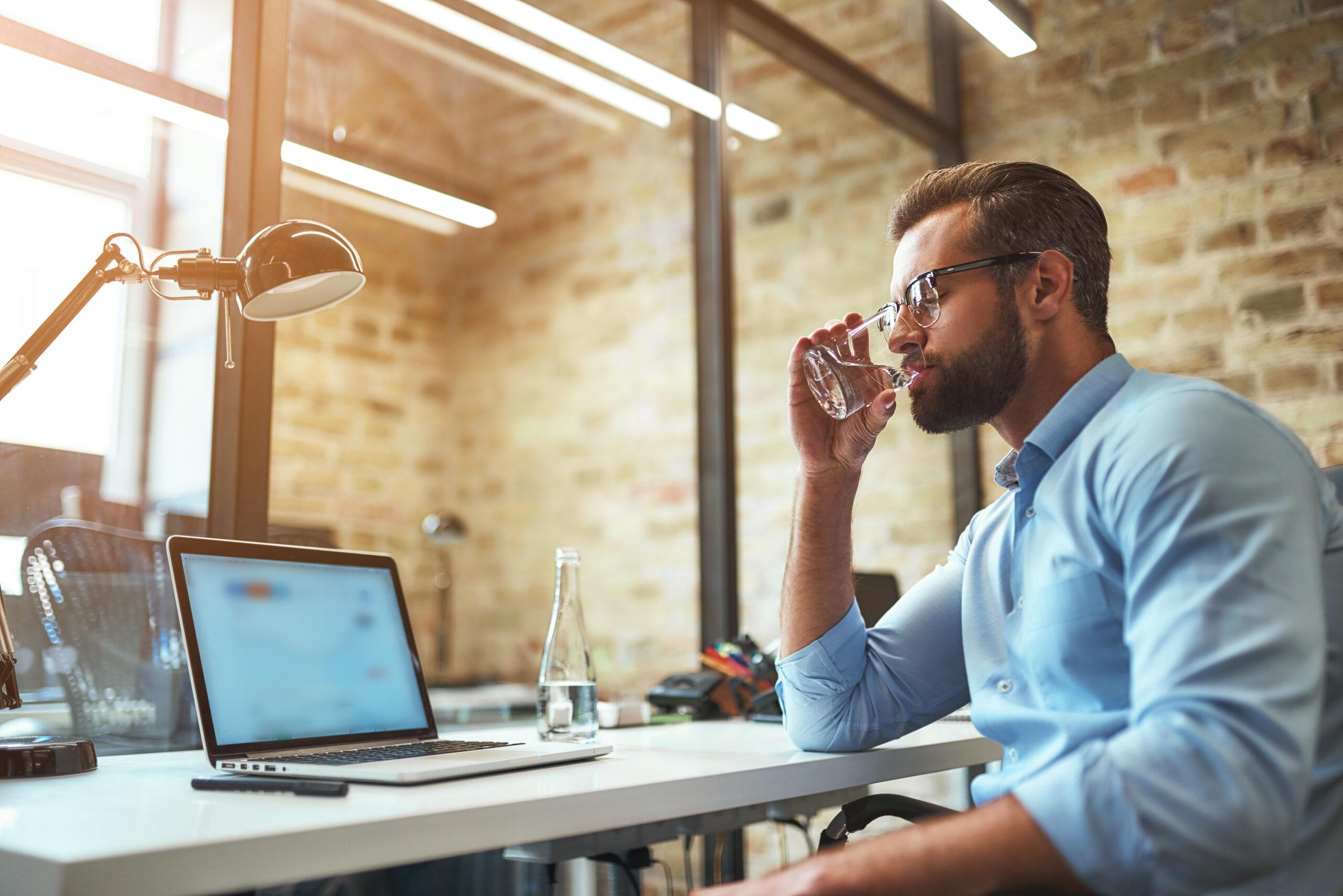 Ein Mann trinkt ein Glas Wasser an seinem Schreibtisch