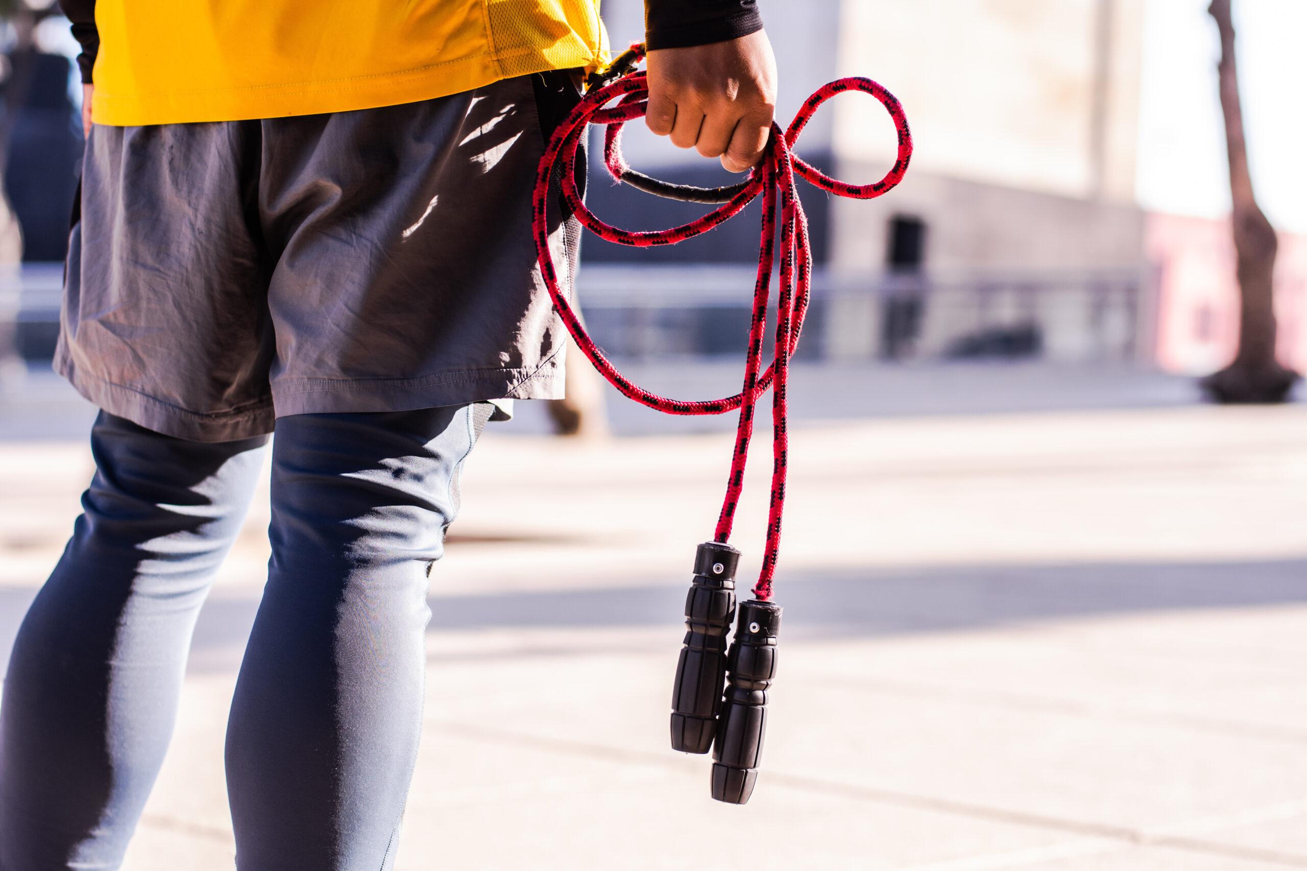 Seilspringen: Ein Mann steht auf einem Platz und hat ein rotes Seil in der Hand