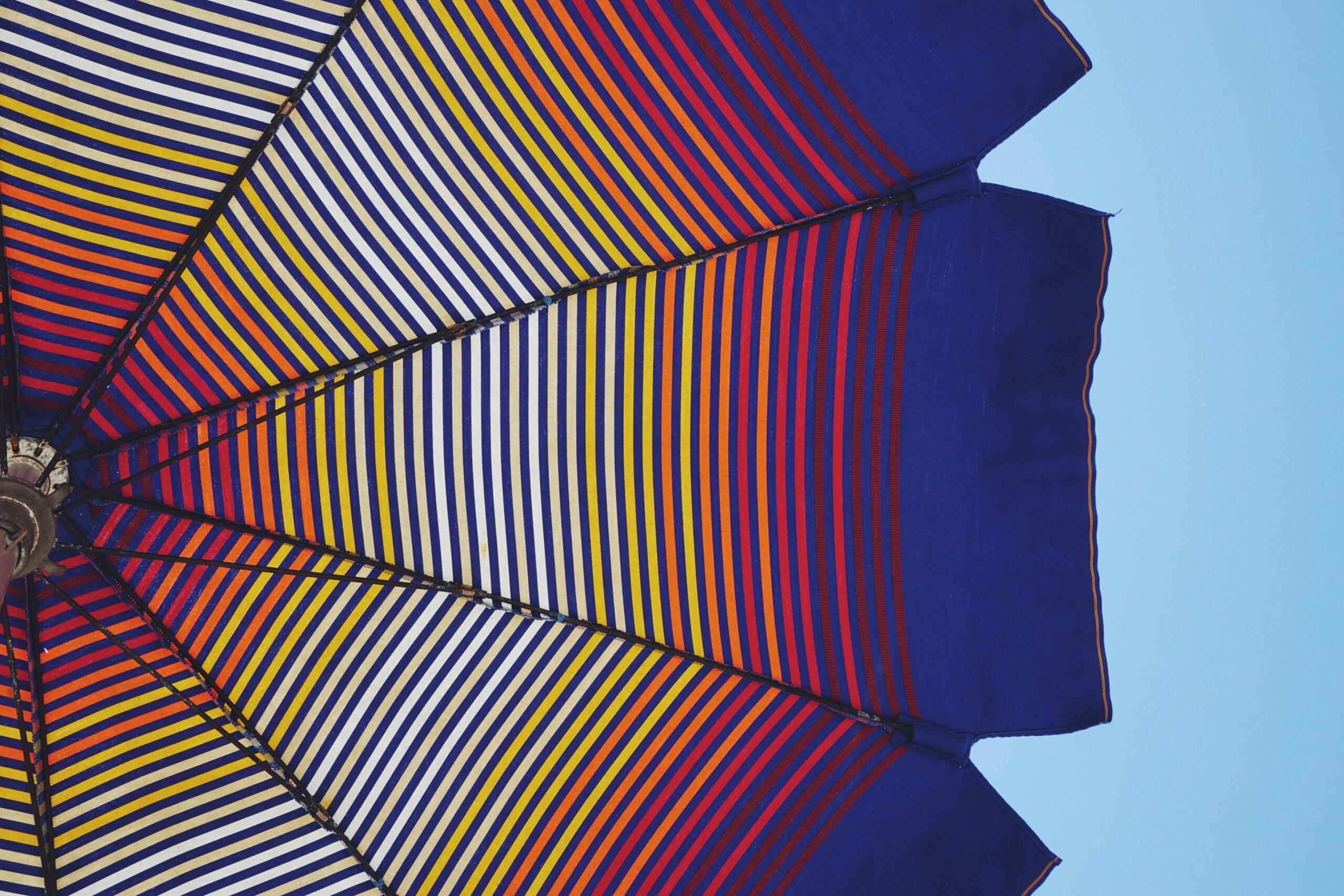 Sonneschutz: Bunter Sonnenschirm vor blauem Himmel