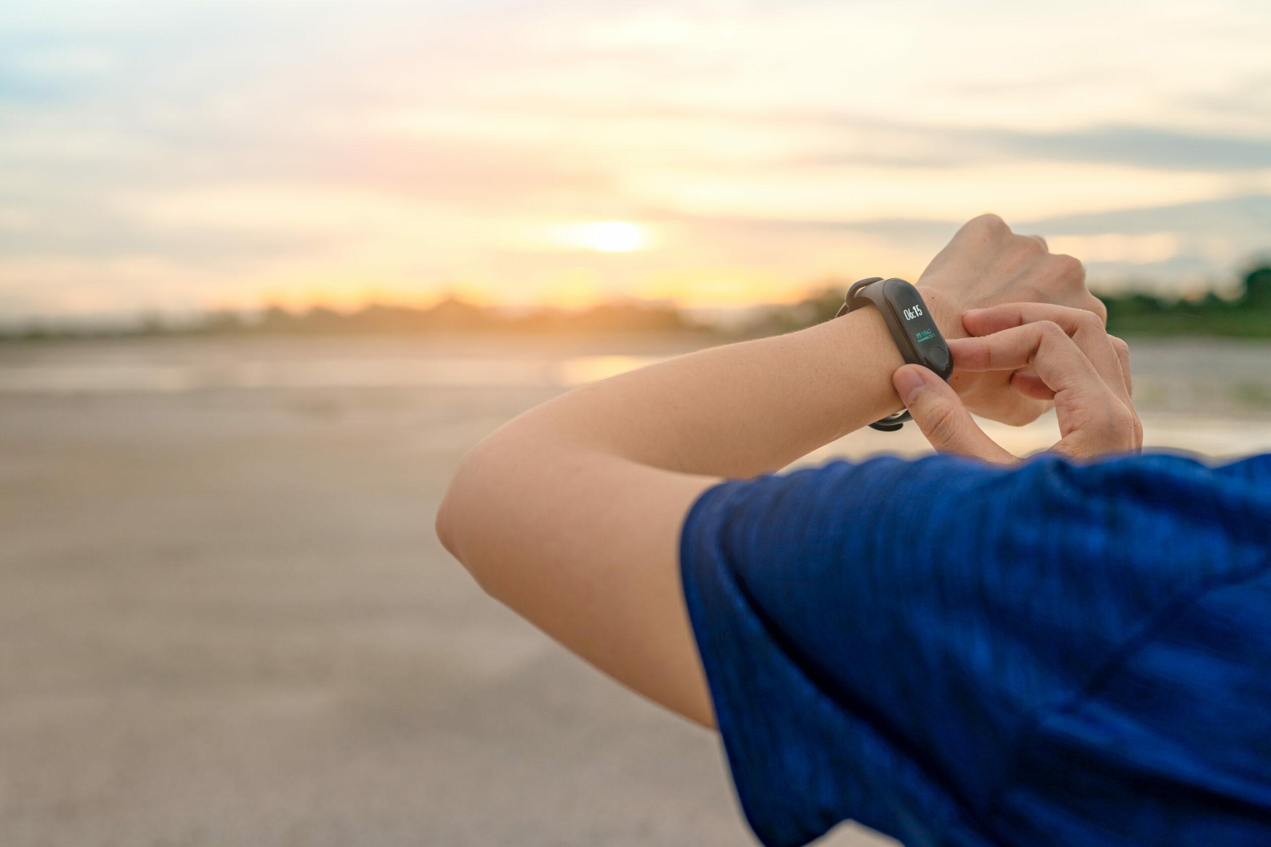Bluthochdruck: Eine Frau steht am Strand und aktiviert ein Wearable